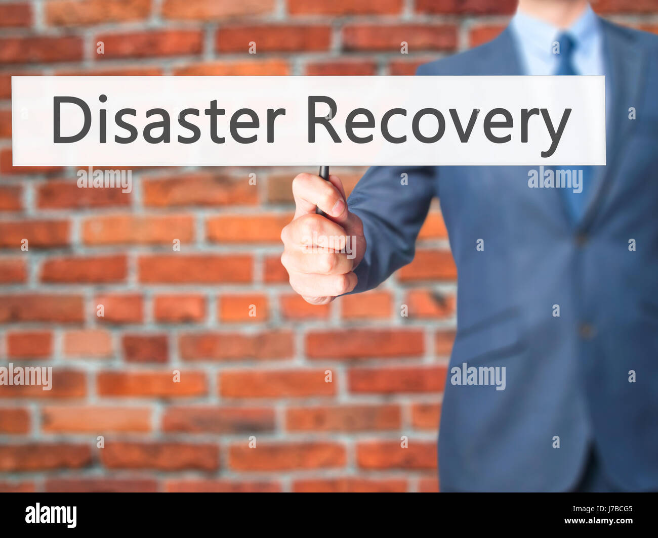 Disaster Recovery - Businessman hand holding sign. Business, technology, internet concept. Stock Photo - Stock Image