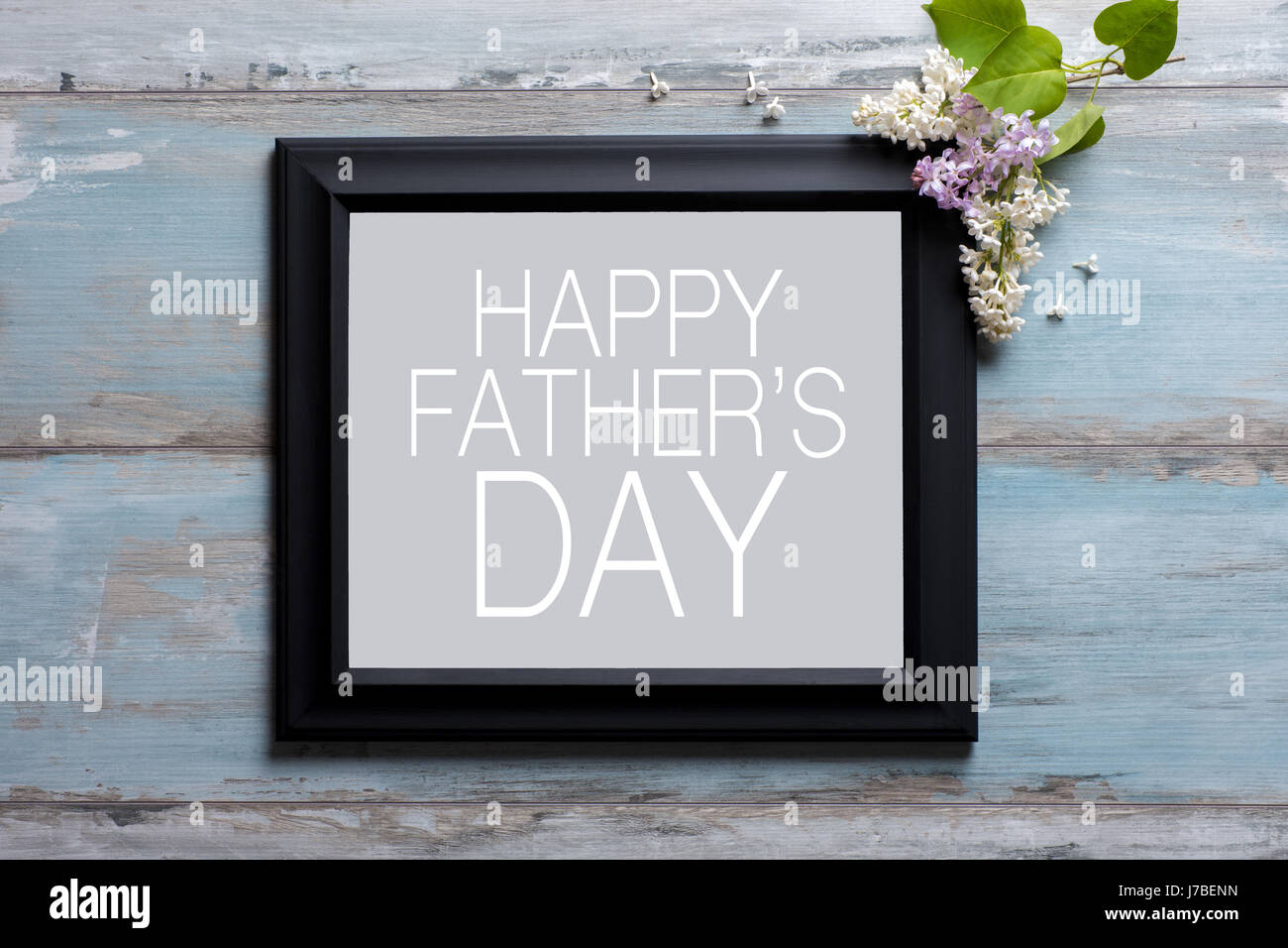 picture frame with lilac flowers and happy fathers day message on blue wooden background