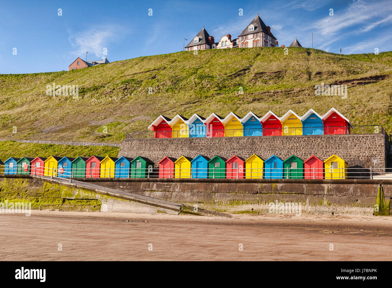 Rows of colorful beach huts on the promenade at Whitby Sands, Whitby, North Yorkshire, England, UK, on a beautiful - Stock Image