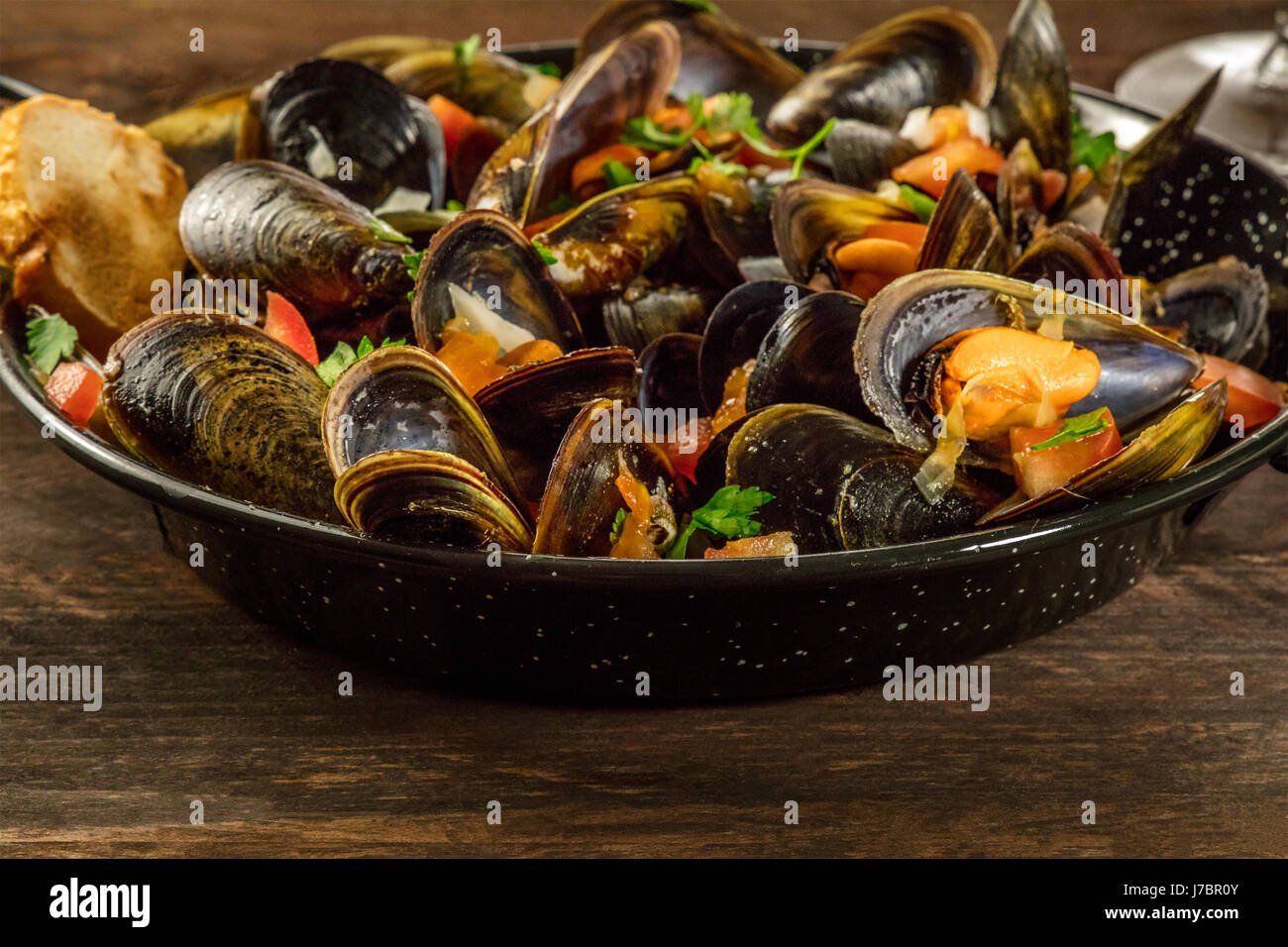 Skillet of marinara mussels on rustic background Stock Photo