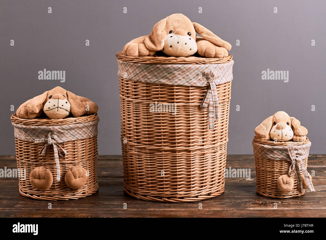 Laundry baskets with soft toys baskets on wooden surface cute household items