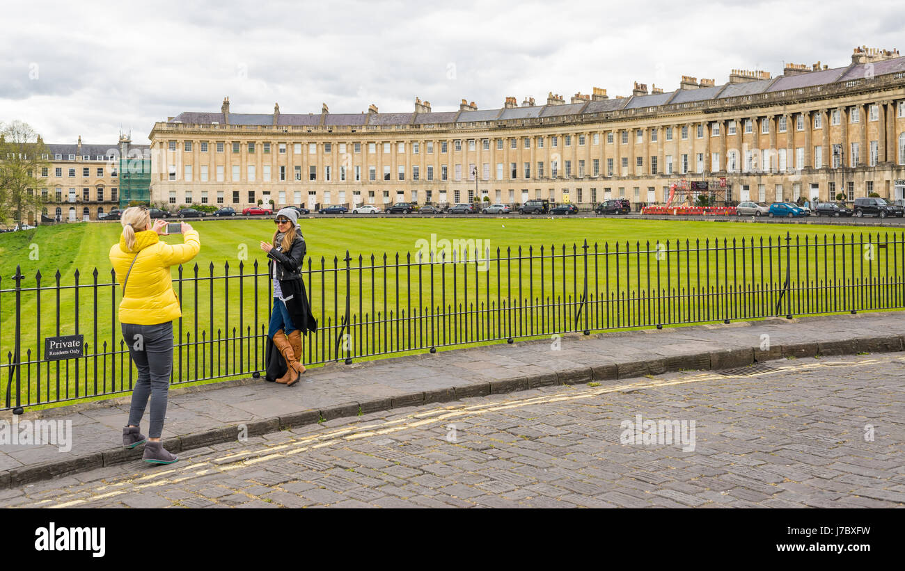 Tourists taking pictures in front of the Royal Crescent in Bath, UK - Stock Image