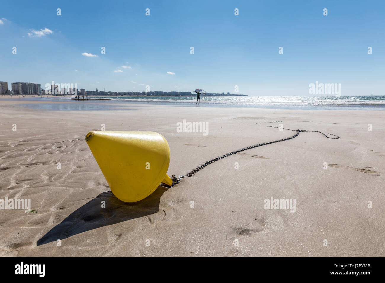 Yellow conical buoy on the beach of Les Sables d'Olonne at low tide Stock Photo
