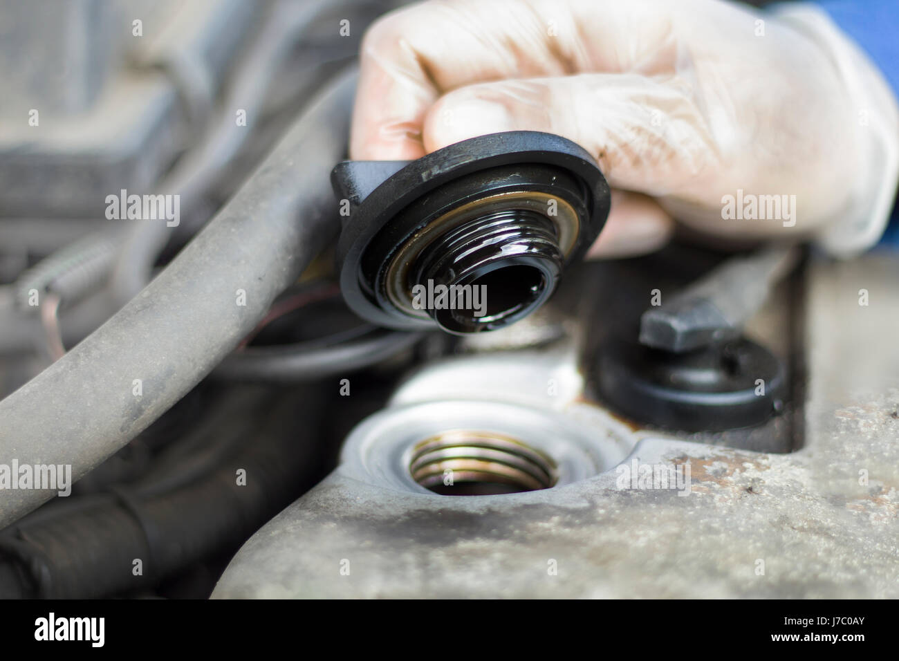 The hands of the car mechanic unscrew the cap of the oil filler. The mechanic in disposable gloves unscrewed the - Stock Image