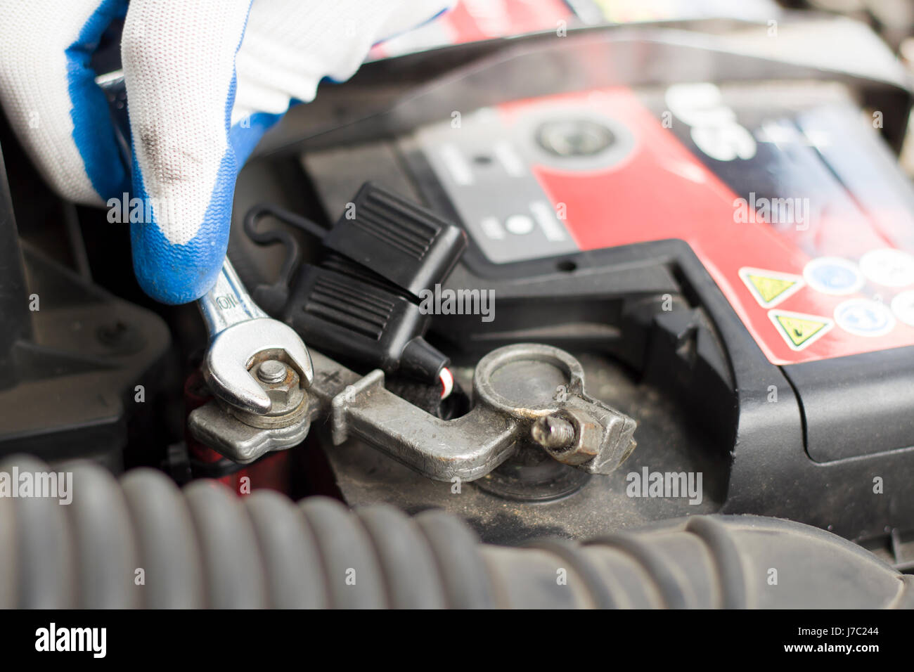 The hands of the car mechanic in disposable gloves unscrew the battery clutch. The hand of a mechanic with a flat - Stock Image