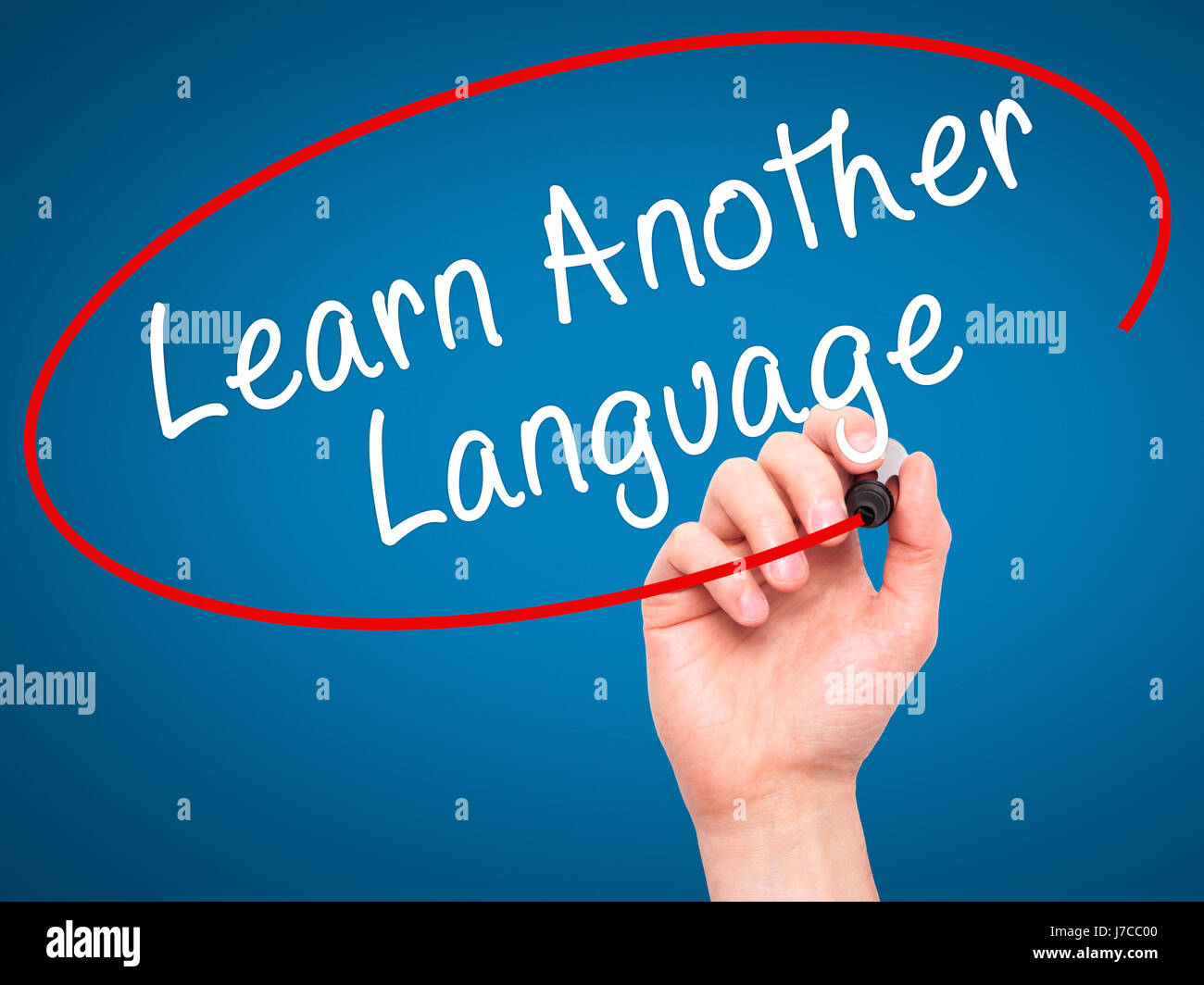 Man Hand writing Learn Another Language with black marker on visual screen. Isolated on blue. Learn, technology, - Stock Image