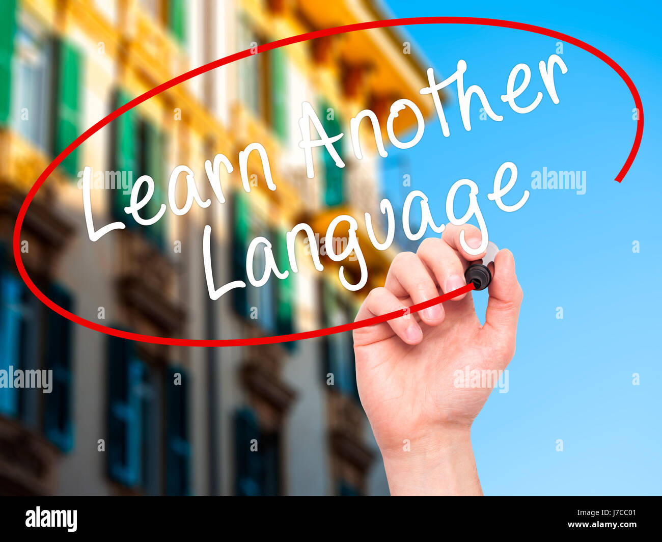 Man Hand writing Learn Another Language with black marker on visual screen. Isolated on city. Learn, technology, - Stock Image