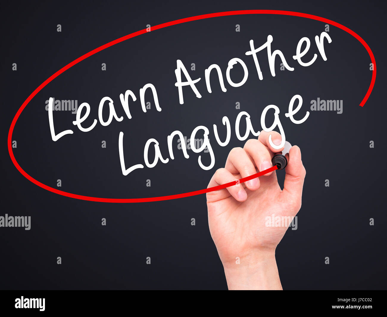 Man Hand writing Learn Another Language with black marker on visual screen. Isolated on black. Learn, technology, - Stock Image