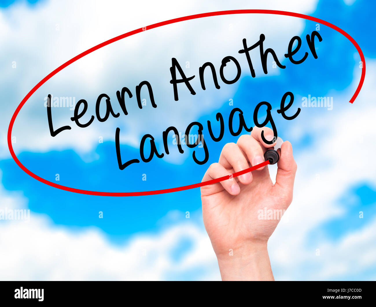 Man Hand writing Learn Another Language with black marker on visual screen. Isolated on sky. Learn, technology, - Stock Image