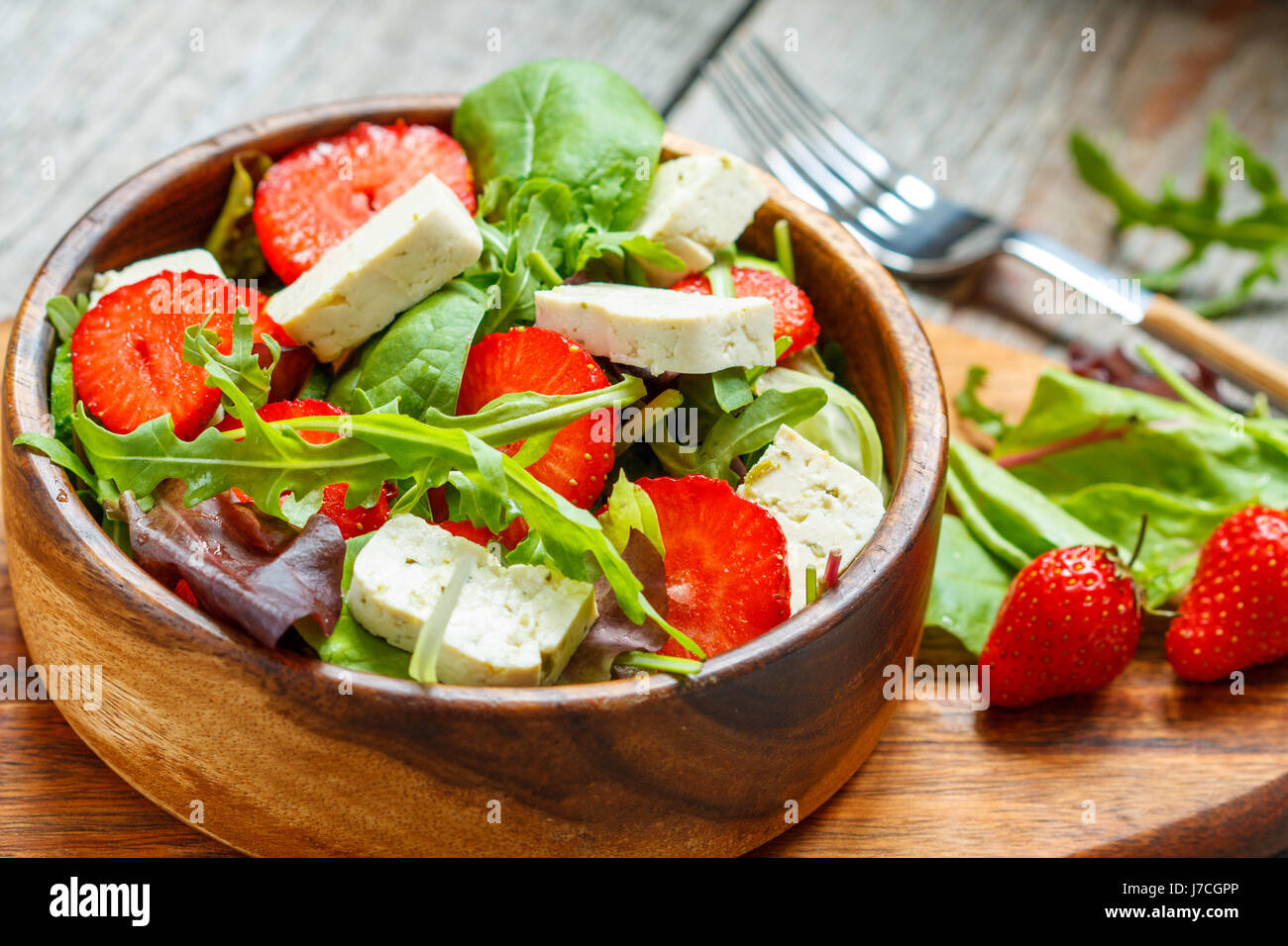 Vegan salad with tofu and strawberries. Love for a healthy vegan food concept - Stock Image
