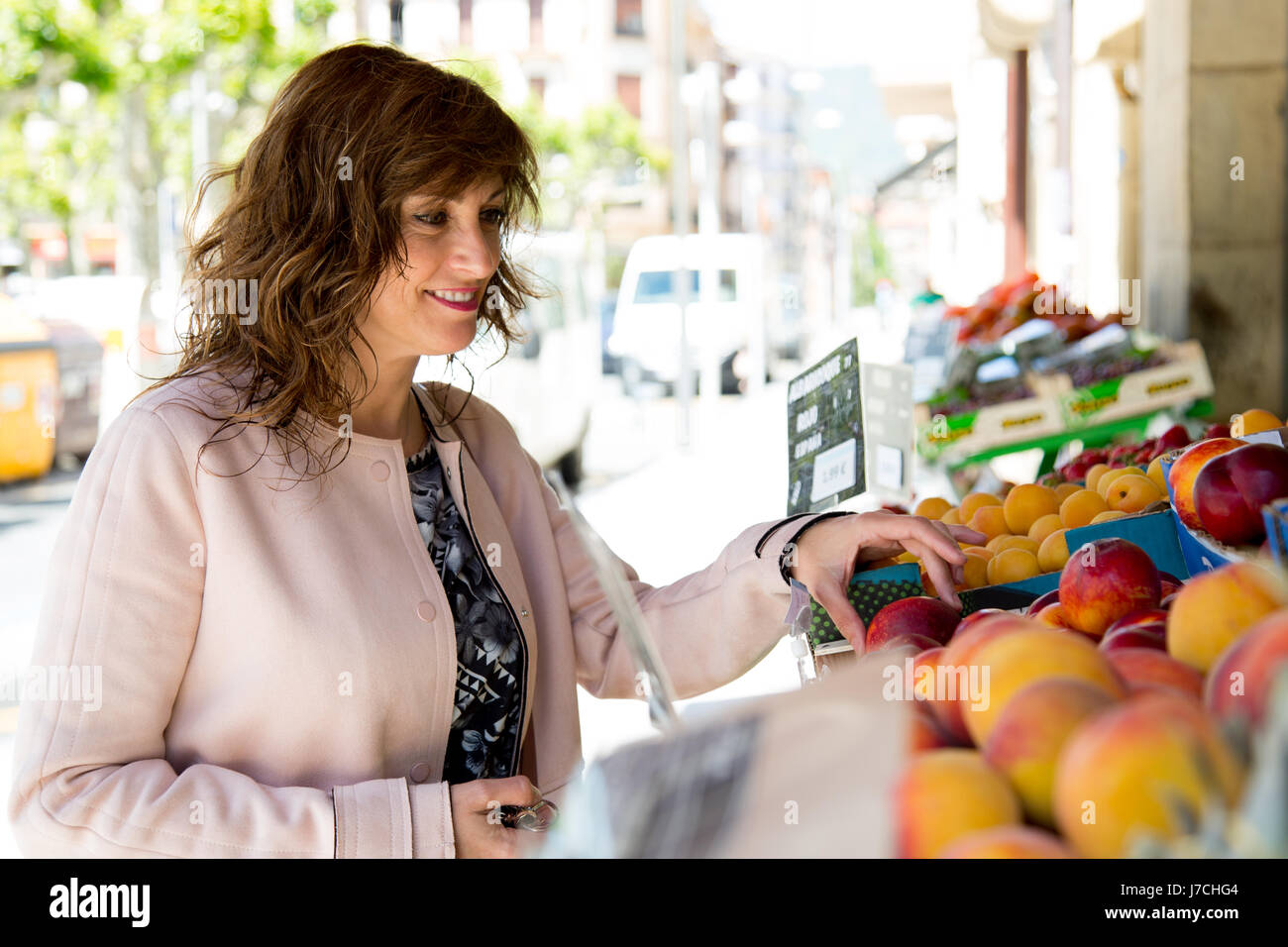 Attractive middle aged woman buying fruit at street market Stock Photo