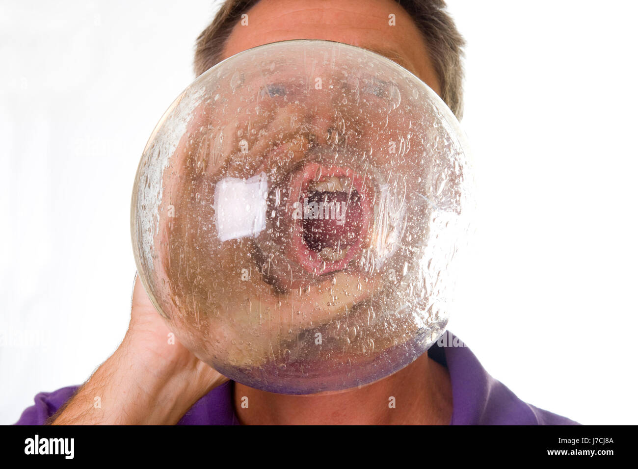 Man shouting through crystal ball with magnified mouth - Stock Image