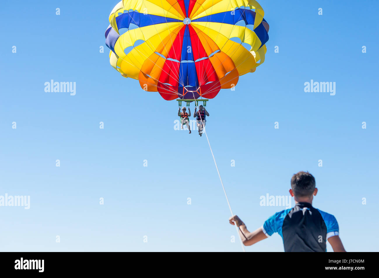 Happy couple Parasailing in Dominicana beach in summer. Couple under parachute hanging mid air. Having fun. Tropical - Stock Image