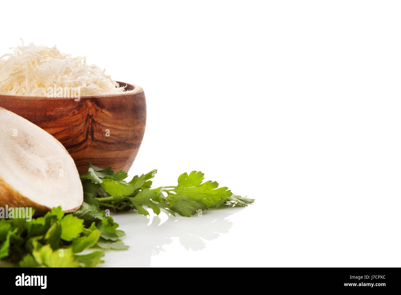 Grated horseradish in wooden bowl isolated on white background. - Stock Image