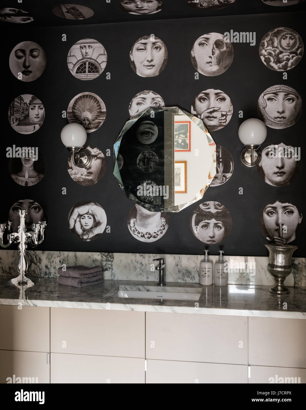 Fornasetti wallpaper in marble bathroom with vintage mirror - Stock Image
