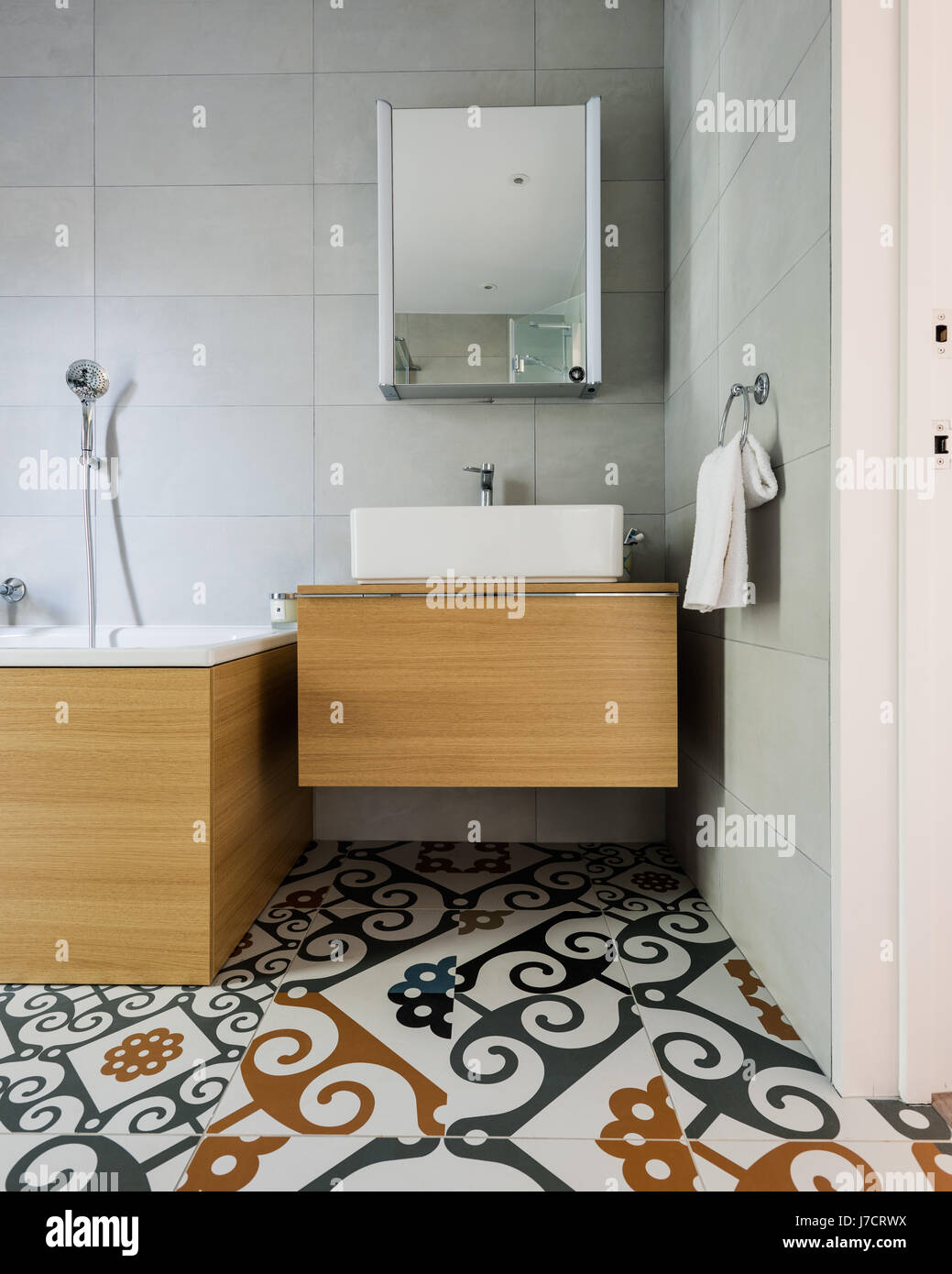 Wooden stand and bath surround with Majolica floor tiles - Stock Image