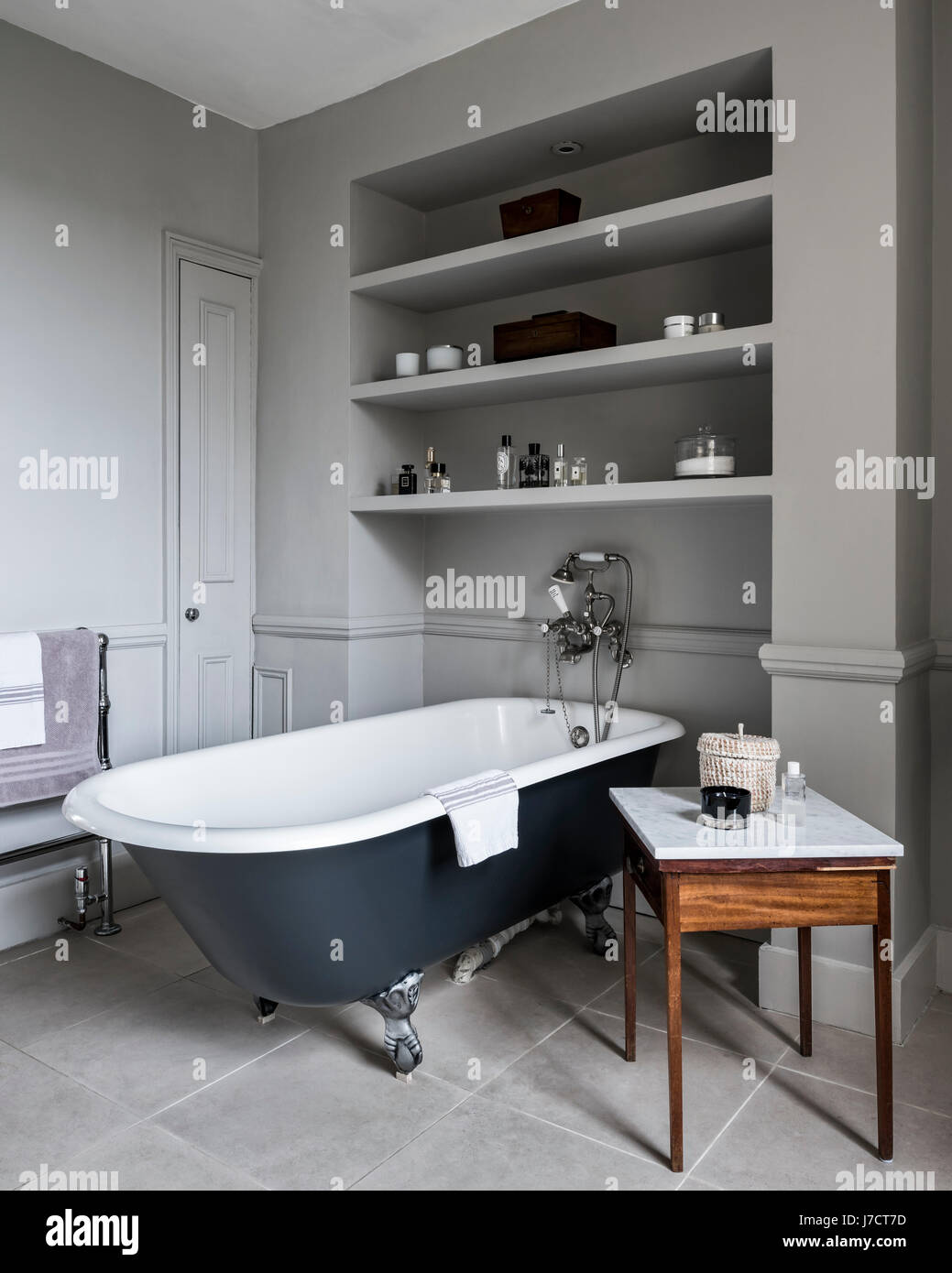 Free-standing roll top bath from Albion in bathroom with antique marble topped table and inbuilt shelving. The outside - Stock Image