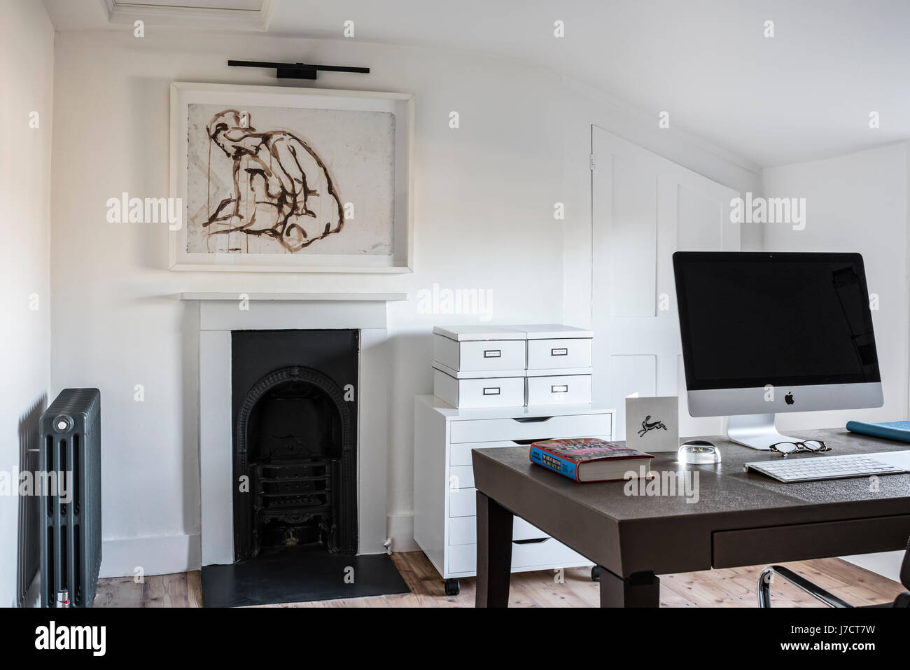 Chic home office with wooden flooring and framed watercolour by Ryan McElhinney, the work table is Philippe Hurel - Stock Image