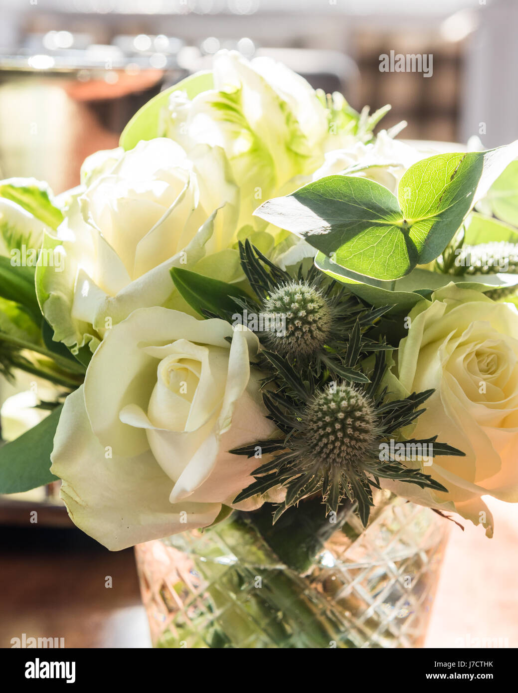 A posey of white roses and thistles in glass vase - Stock Image