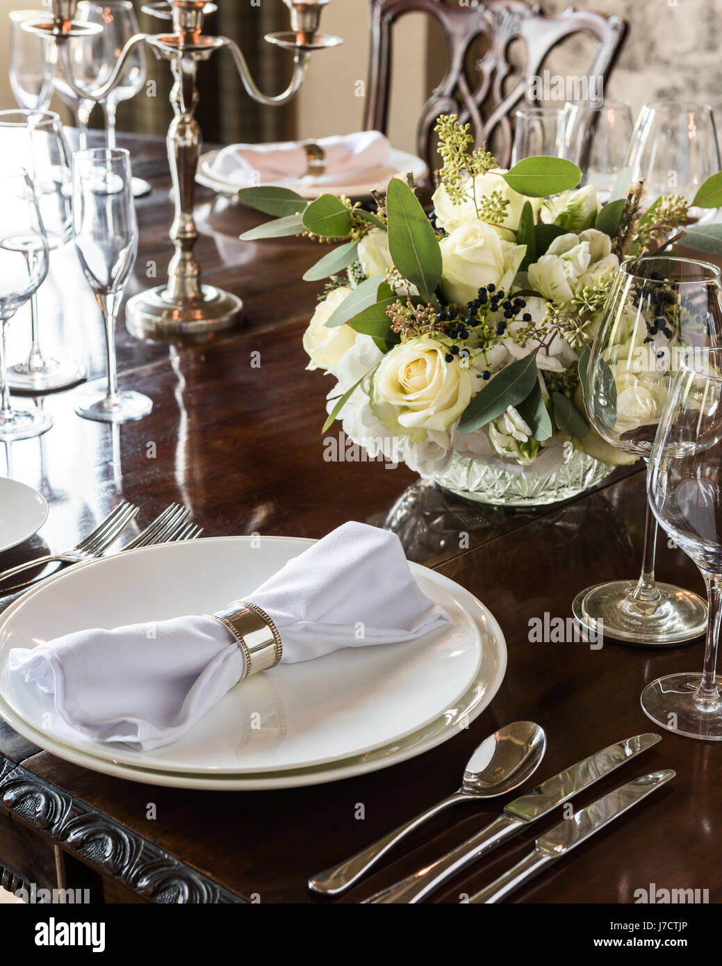 Formal dining place laid with silver cutlery and posey of white roses - Stock Image