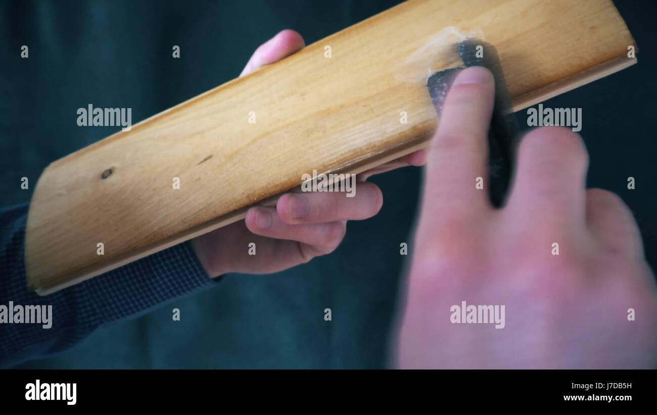 polishing wooden plank with sandpaper - Stock Image