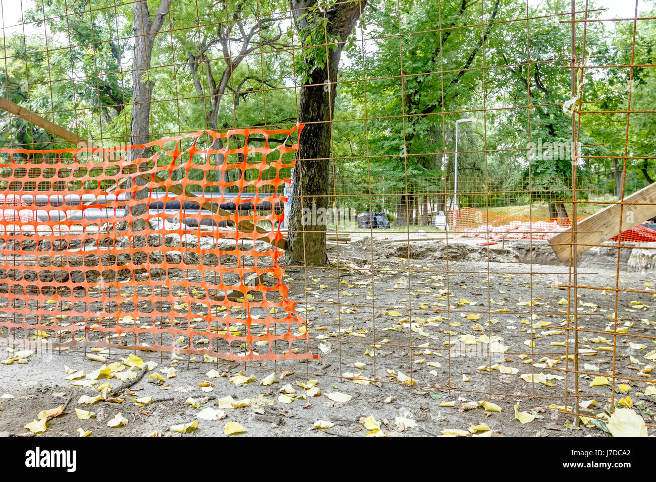 Confined space with orange, plastic, safety net is placed around the building site in deciduous park. - Stock Image