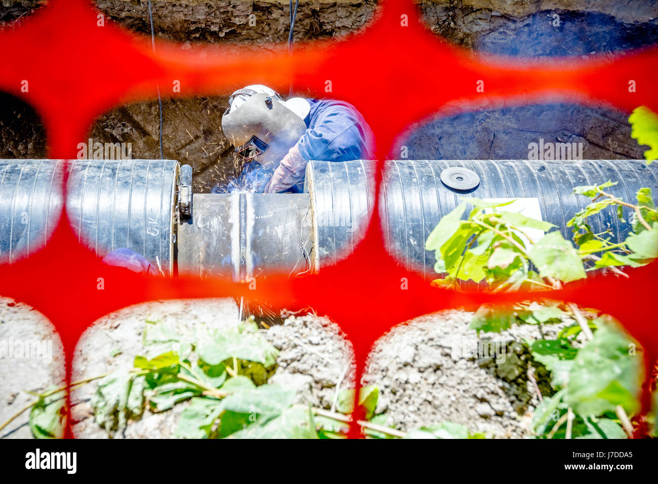 Welder is in trench arc welding pipeline. Confined space with orange, plastic, safety net - Stock Image
