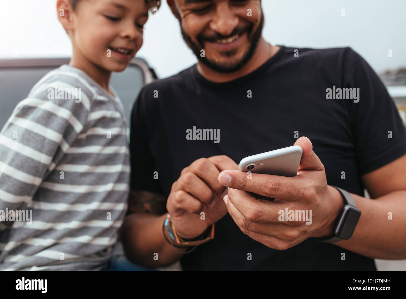 Close up of happy father and son in front of the car looking at the mobile phone. Young man and little boy using - Stock Image