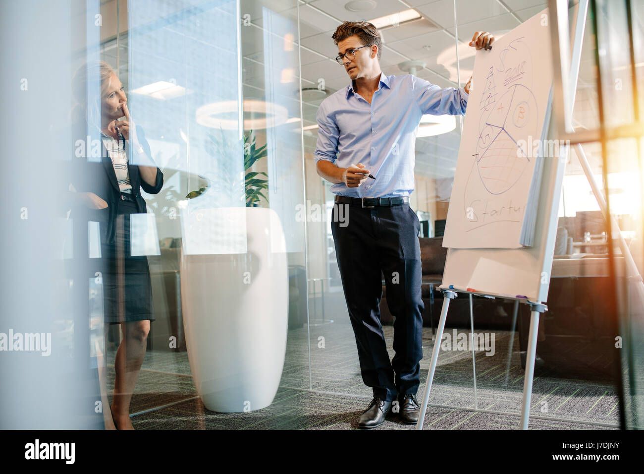 Office worker standing near flip chart with diagram. Mature businessman giving a presentation on a flipchart to - Stock Image