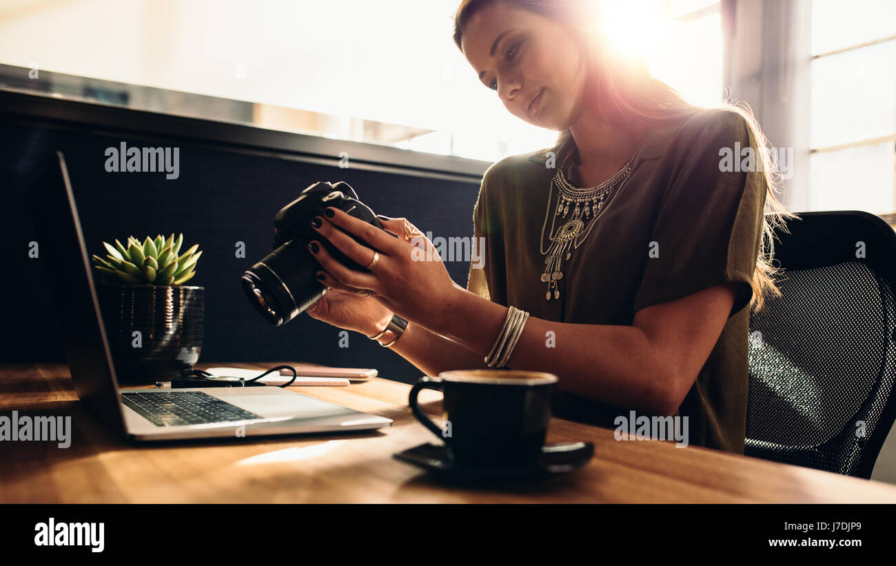 Young woman looking at camera while working on laptop. Photographer with her camera and laptop on her desk. - Stock Image