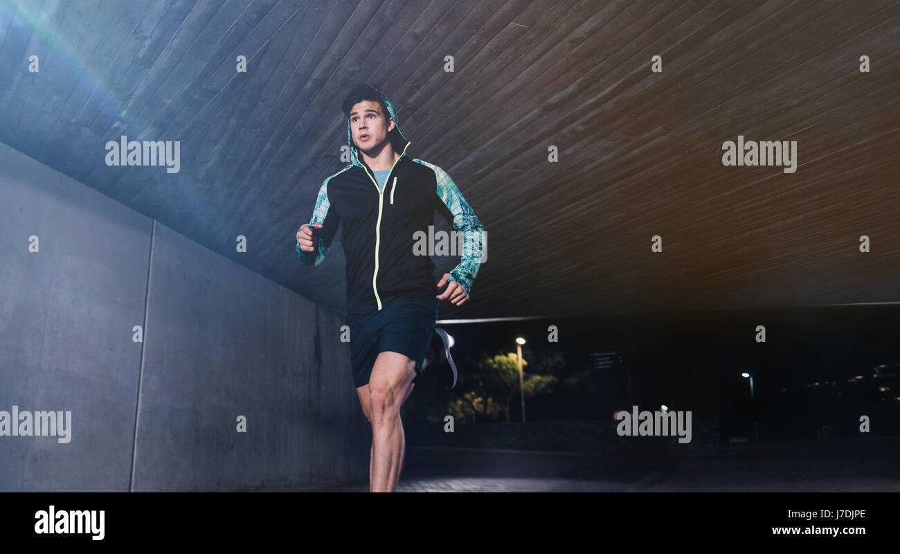 Young man jogging at night in city. Fit male athlete running under a bridge. Stock Photo