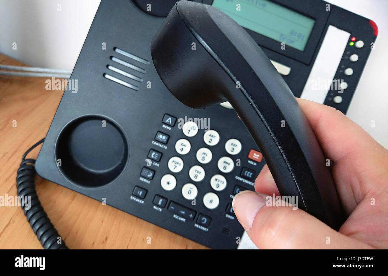 Close-up of picking telephone handset up for making a call. - Stock Image