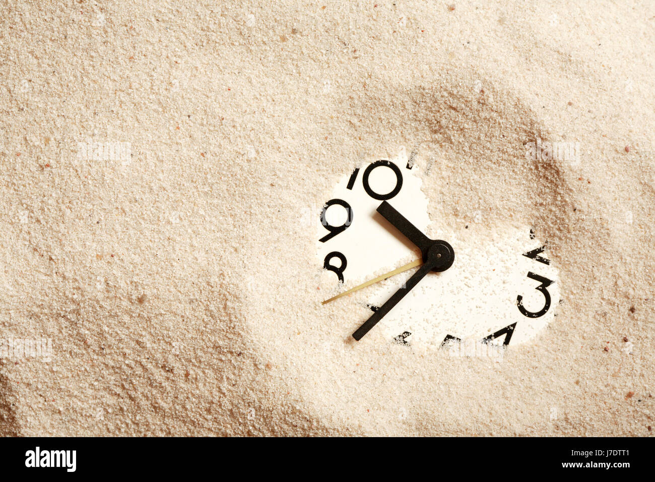 Time concept. Sand background with clock face - Stock Image