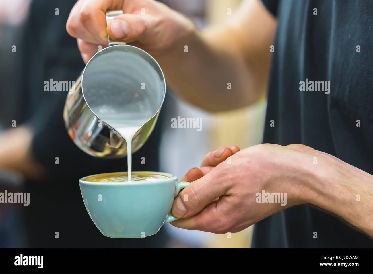 Barista in coffee bar preparing proper cappuccino pouring frothed milk into cup of coffee, making latte art, pattern - Stock Image