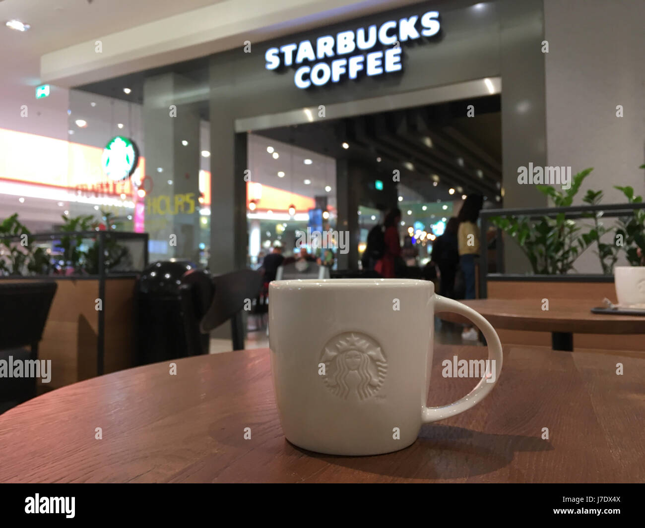 Krakow, Poland - May 21, 2017: Starbucks coffee sign and coffee tables in front of the coffeehouse entrance. Starbucks - Stock Image