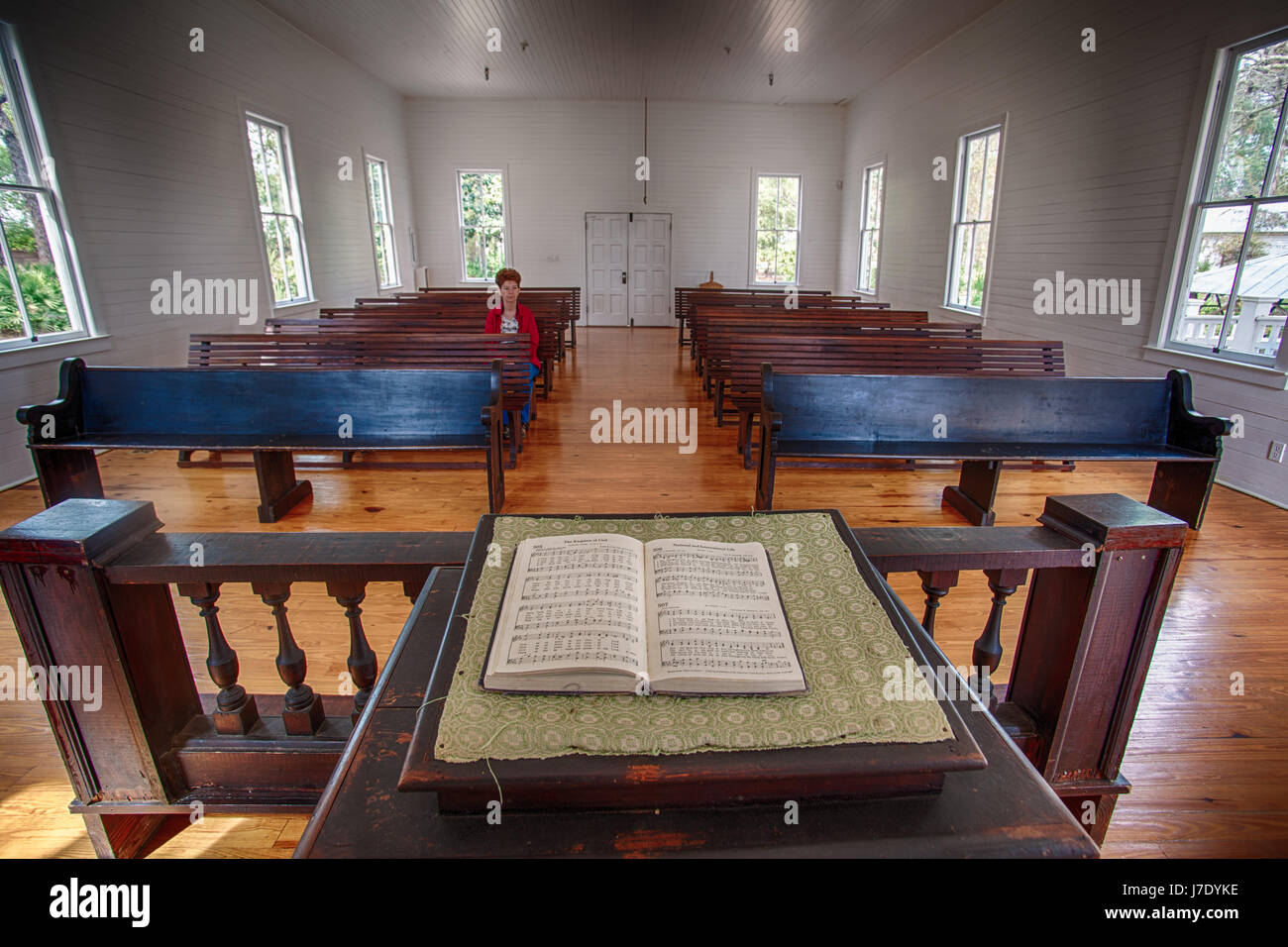 Woman sitting in a pew in an empty chapel - Stock Image