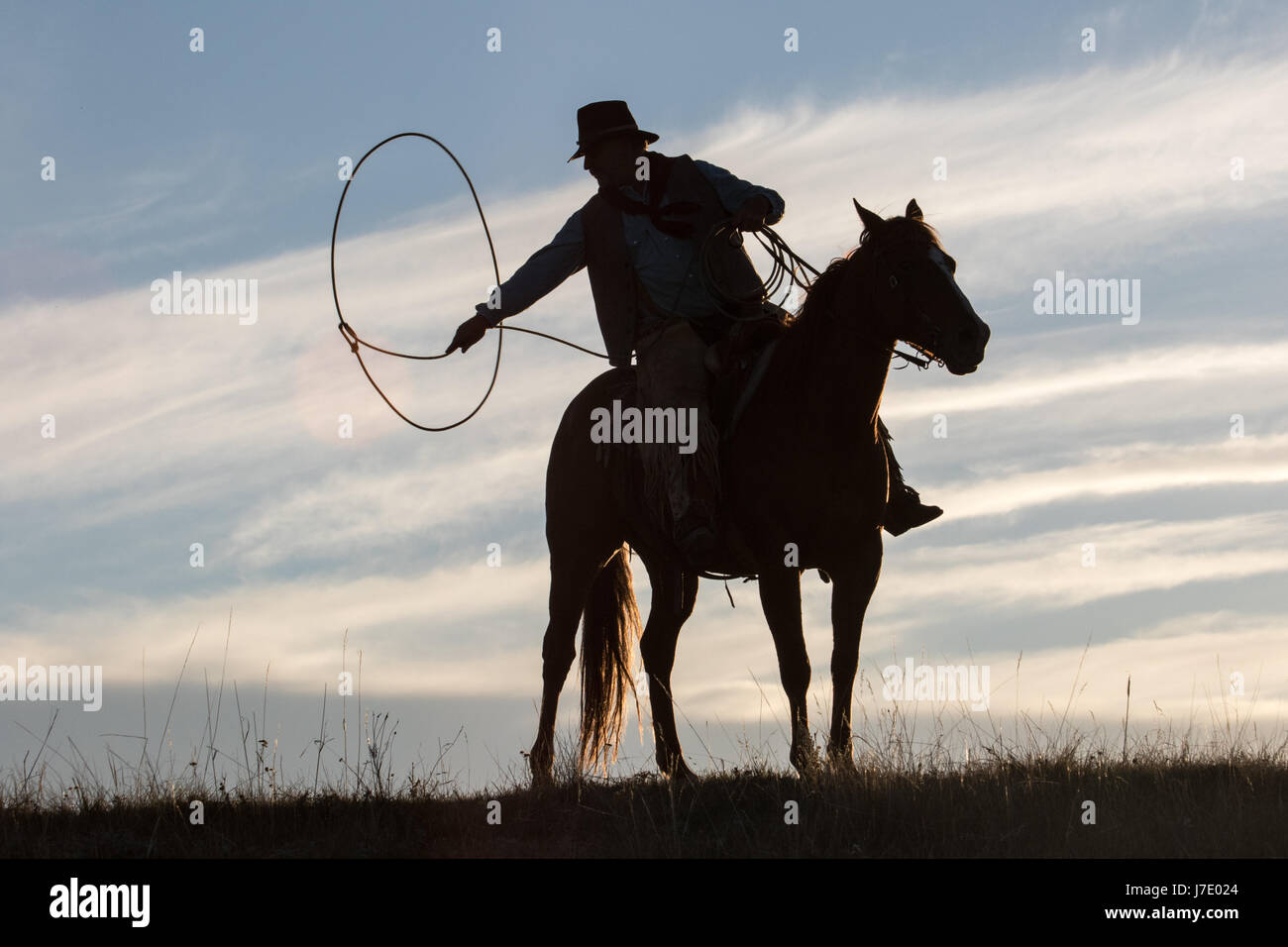cowboy spinning lasso at sunset - Stock Image