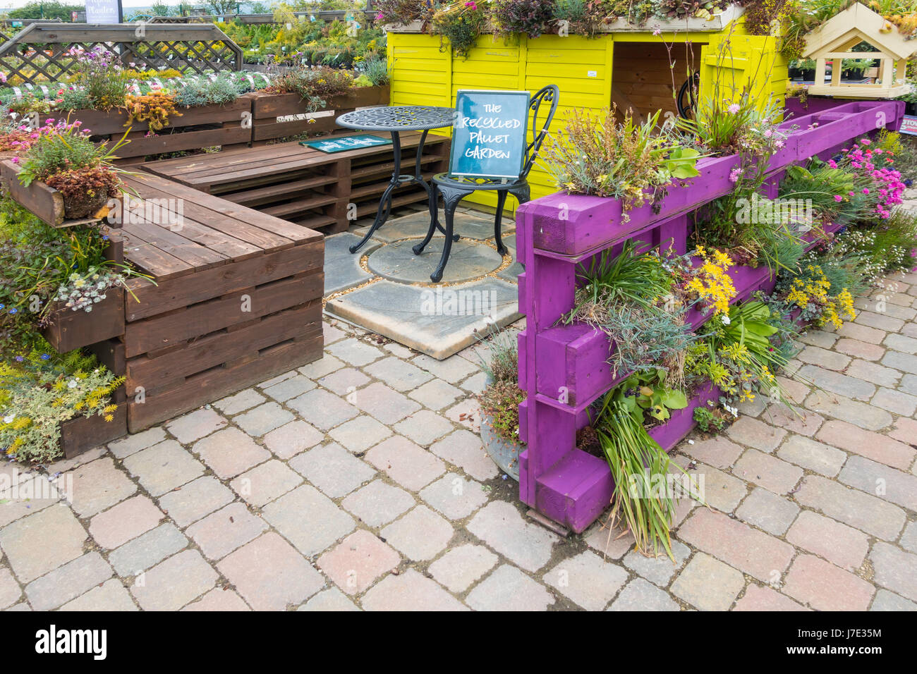 A recycled pallet display in a garden centre with furniture made