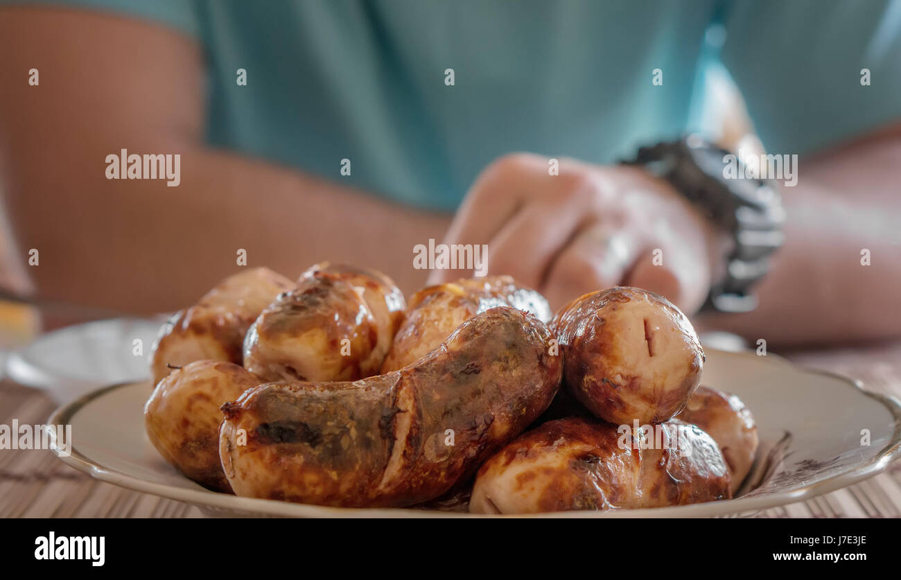 Delicious, juicy sausages roasted on a spit over an open fire are on the plate . A horizontal frame. - Stock Image