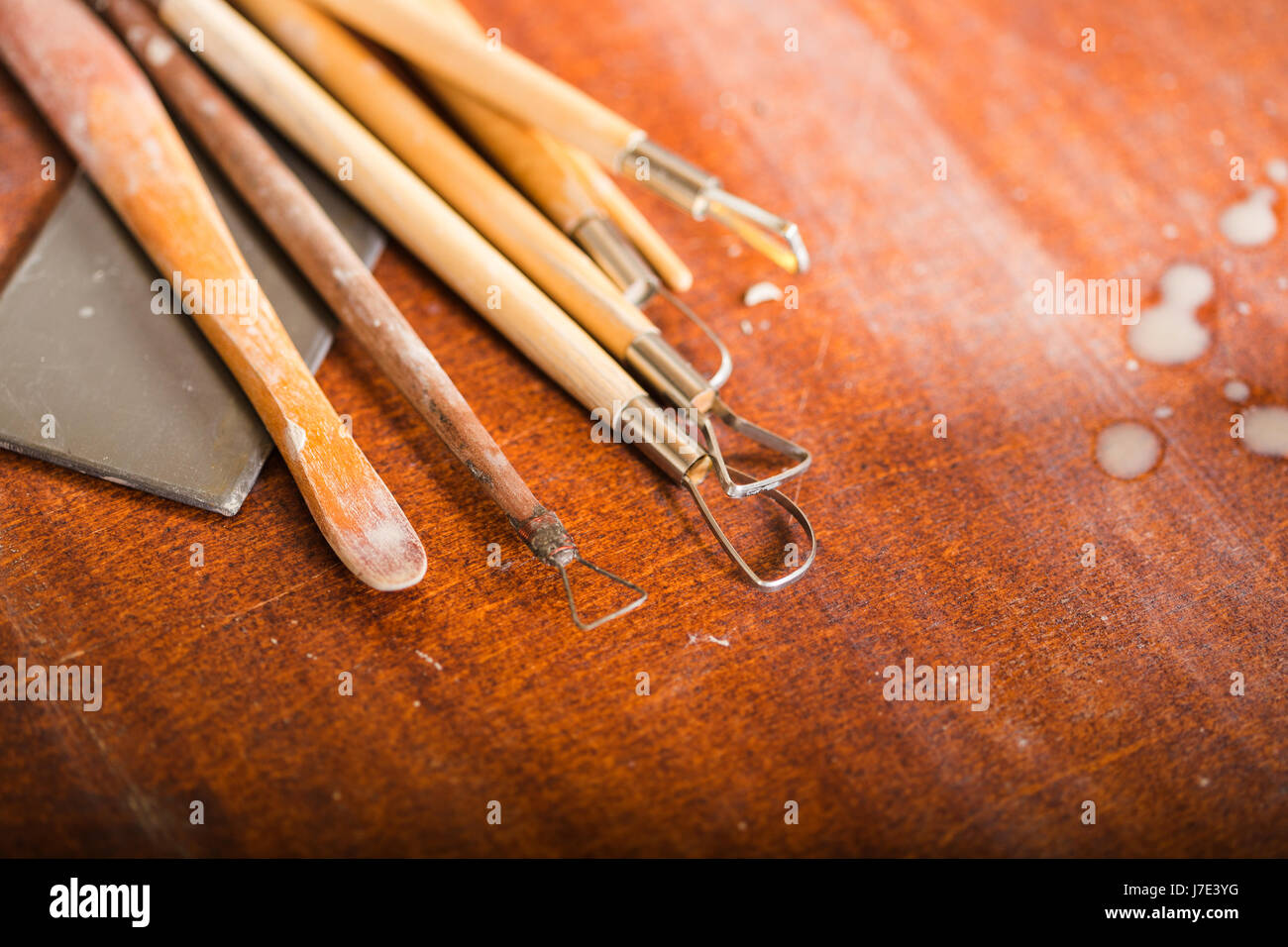 pottery, workshop, ceramics art concept - close-up on sculpting tools set on wooden table, clay stacks, different - Stock Image