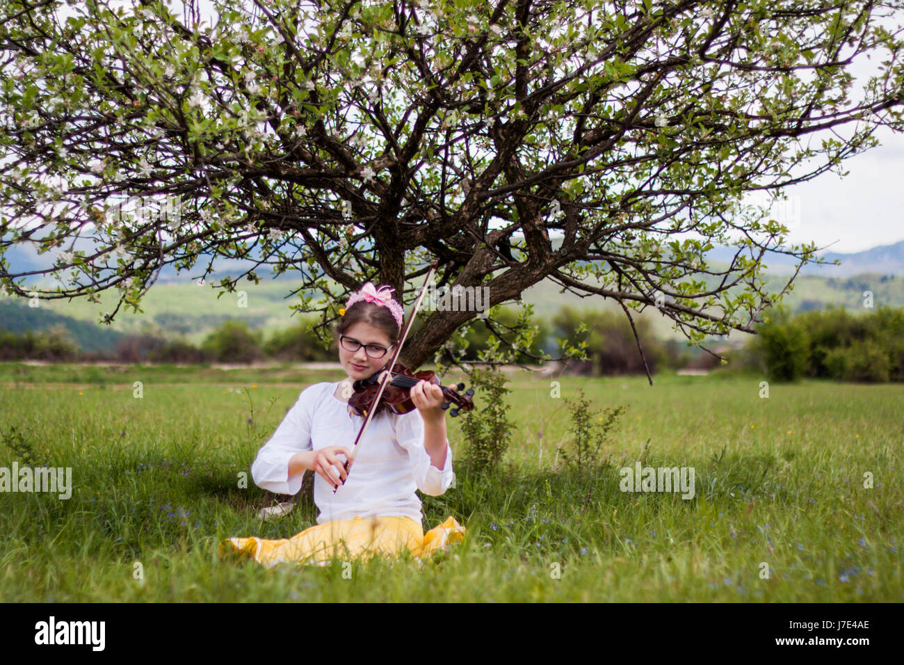 Beautiful blonde girl sitting on a beautiful green grass full of flowers and enjoy the sounds of the violin, girl Stock Photo