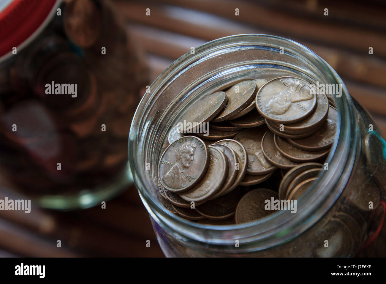 Jar filled with Pennies us currency one cent piece Stock Photo