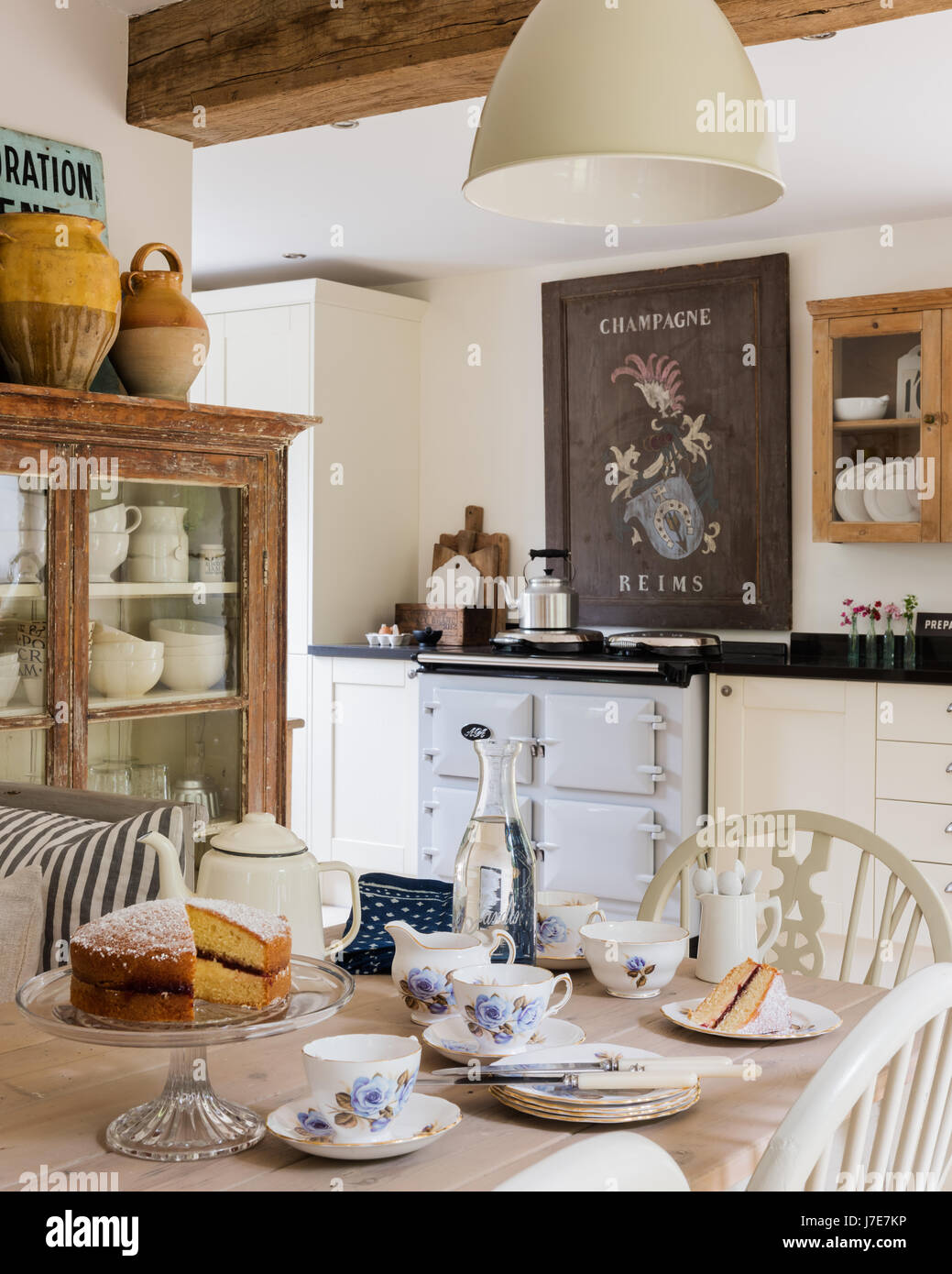 Vintage French wooden champagne sign above Aga in rustic kitchen with French feel. The table is laid for tea with Victoria sponge cake and the display Stock Photo