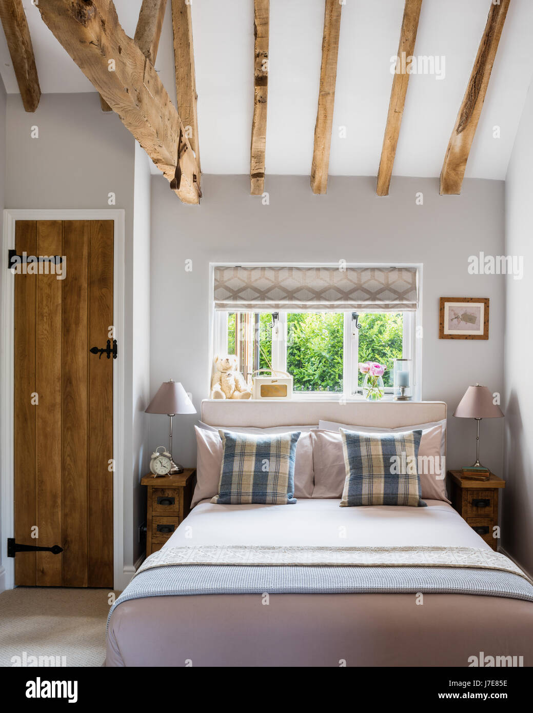 Cosy bedroom with wooden ceiling beams and narrow plank bedside