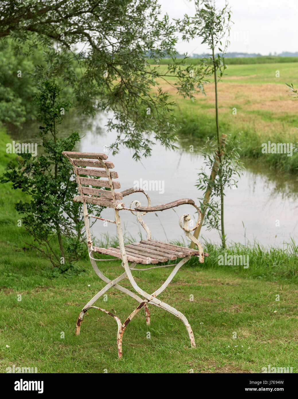 Old chair with peeling paint on riverbank in rural countryside - Stock Image
