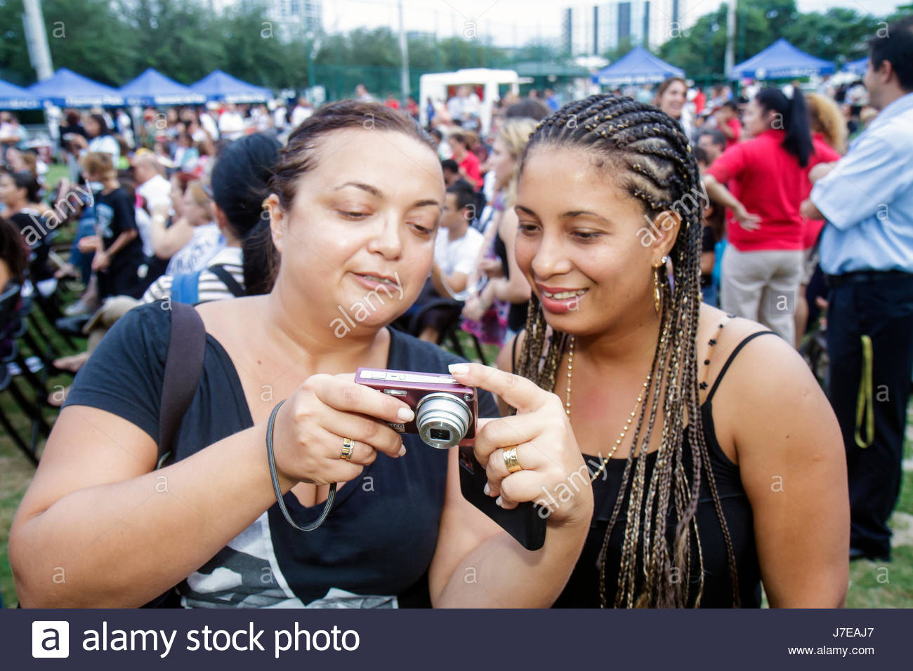 Miami Beach Florida North Beach Northshore Park Hispanic Heritage Festival Black woman camera looking at picture - Stock Image