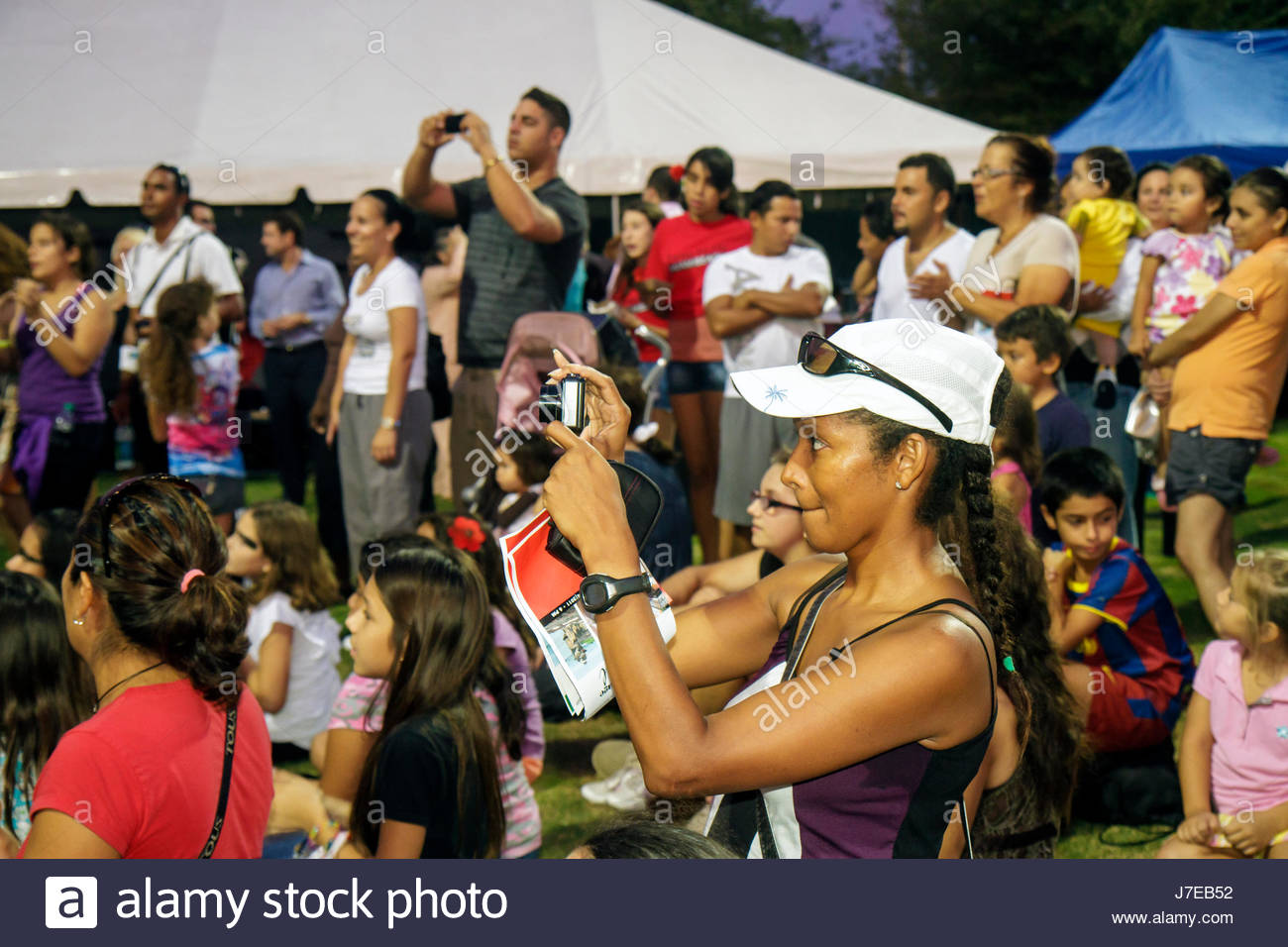 Miami Beach Florida North Beach Northshore Park Hispanic Heritage Festival audience Black woman camera taking picture - Stock Image