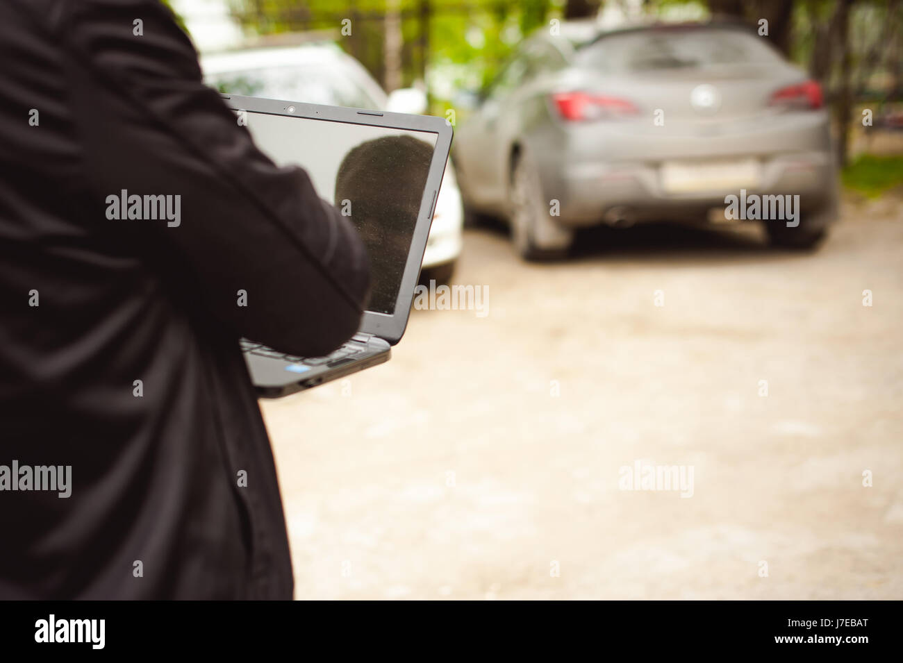 man with a laptop in parking lot in yard near car is doing manipulations with cyber system, concept - Stock Image