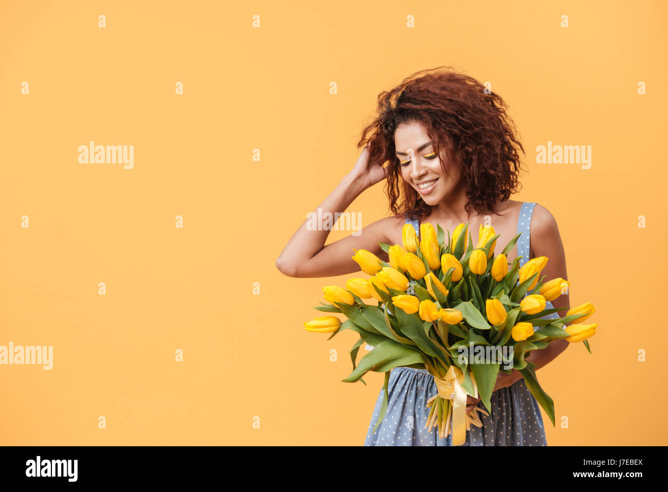Attractive African woman in blue dress holding bouquet of flowers over  yellow background 4f9682fda
