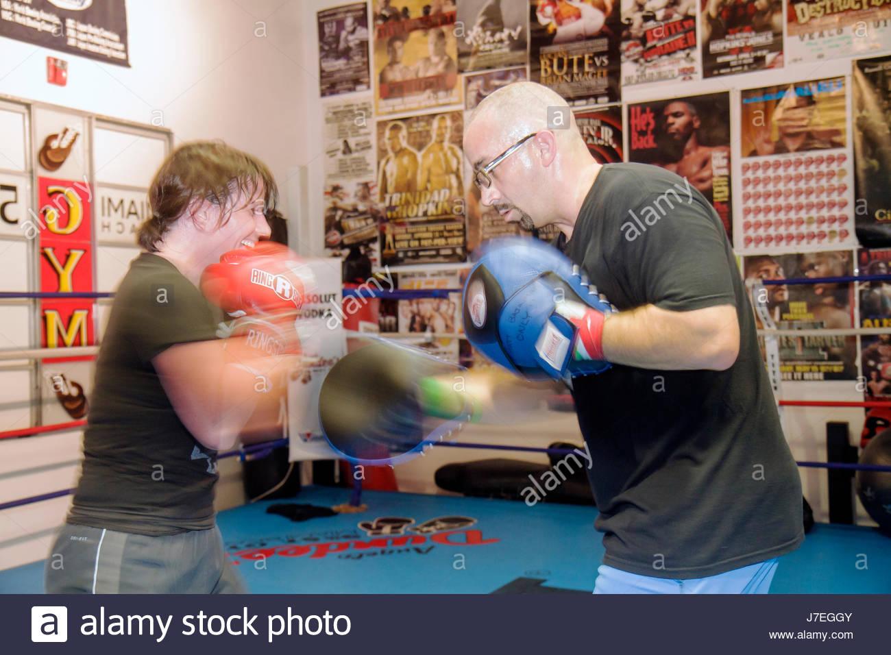 Miami Beach Florida Washington Avenue 5th Street Gym boxing training woman man trainer ring punching jabbing workout - Stock Image